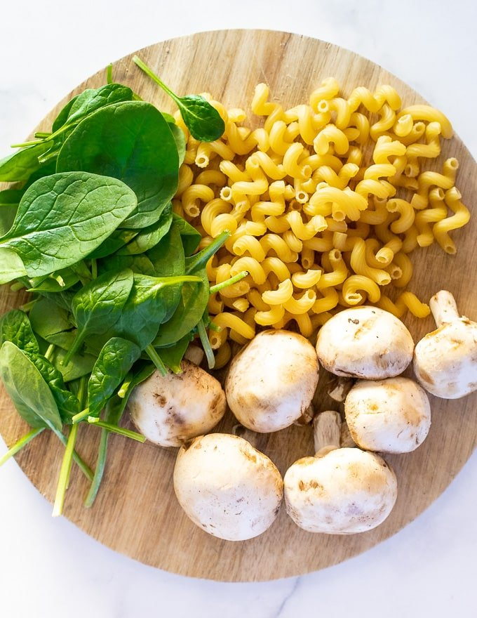 pasta spirals, mushrooms and spinach on a wooden board, ready to make creamy vegan mushroom pasta