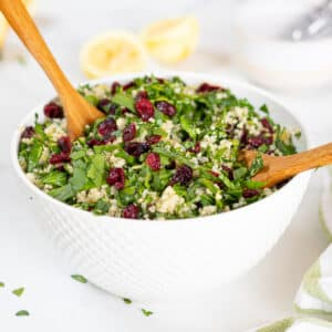a whote bowl full of quinoa cranberry spinach salad with salad servers in it