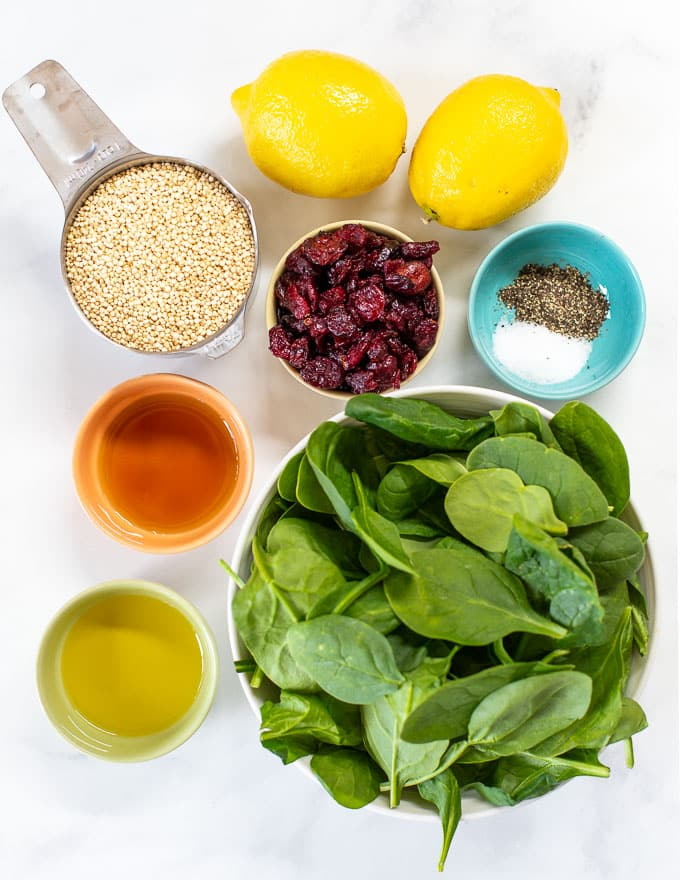 all of the ingredients to make quinoa cranberry salad laid out on a white backdrop
