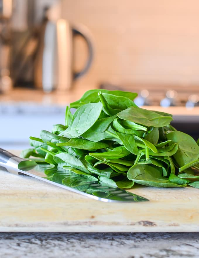 spinach on a cutting board with a sharp knife