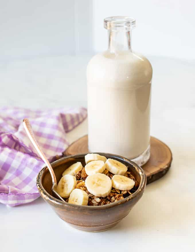 A bowl of granola and banana and a bottle of cashew milk