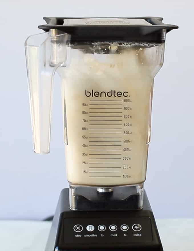 cashews and water being blended up in a blender