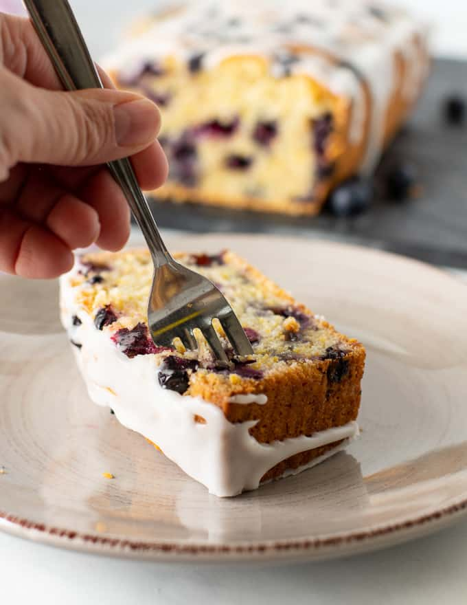 someone sticking a fork into a slice of lemon blueberry loaf