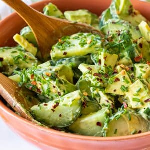 Cucumber Avocado Salad with fresh dill in a bowl with salad servers