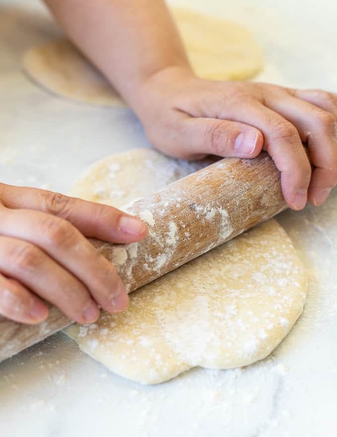 flatbread dough being rolled out with a rolling pin