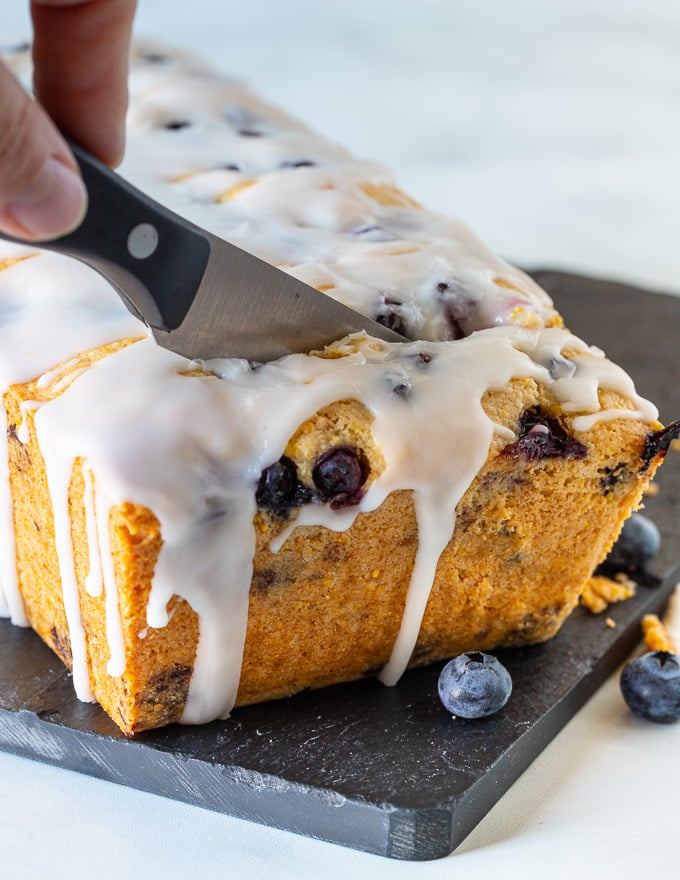 Gluten-free lemon cake with blueberries being cut