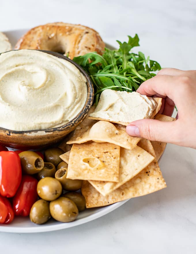 vegan cream cheese spread on a cracker with a hand taking it form a platter