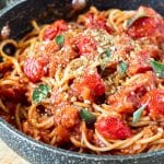 Spaghetti tossed in cherry tomato sauce and topped with herbs and vegan brazil nut parm