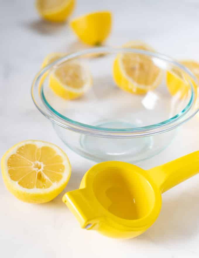 lemon juicer, bowl and lemon halves for making matcha lemonade