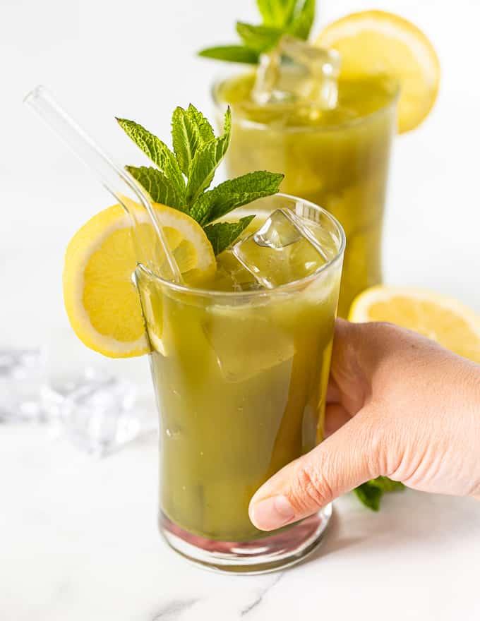 a hand picking up a glass of matcha lemonade