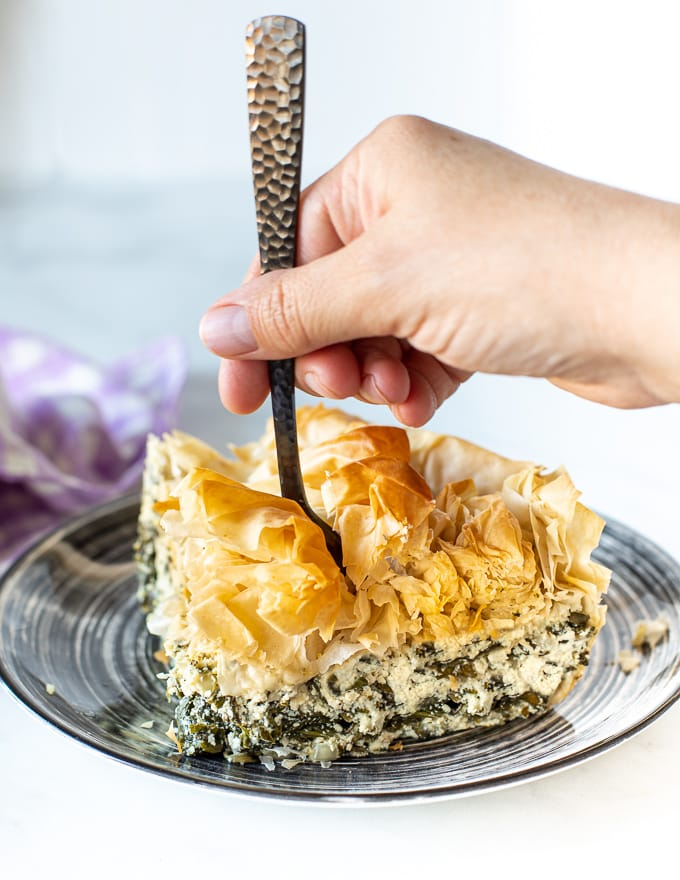 someone sticking a fork into a slice of vegan spanakopita
