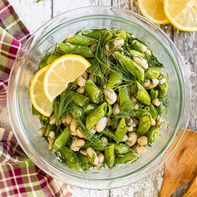 Sugar Snap Pea Salad in a bowl. garnished with lemon and fresh dill.