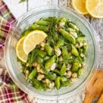 Sugar Snap Pea Salad in a bowl with lemon slices and fresh dill garnish