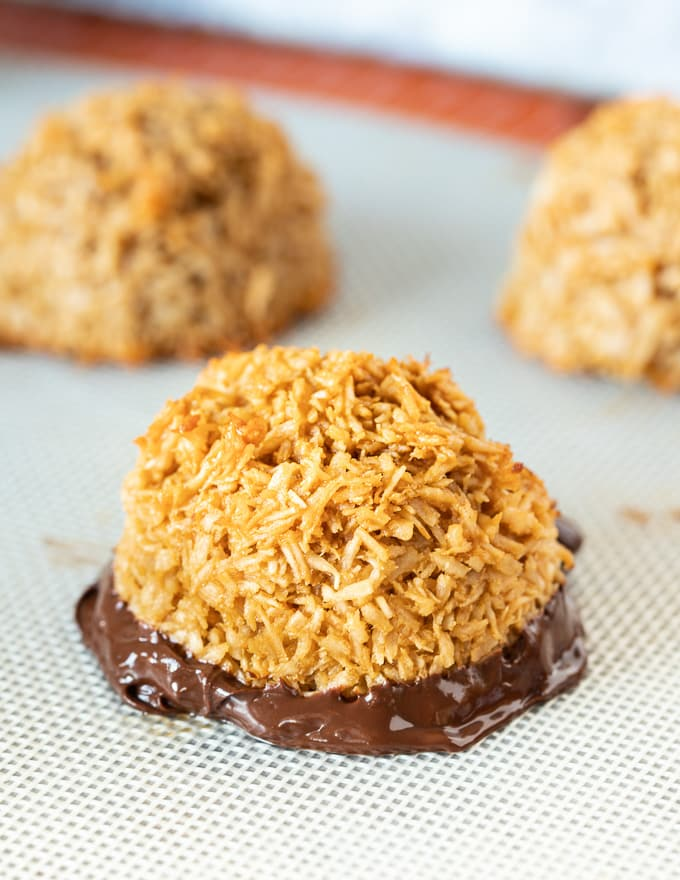 a vegan coconut macaroon with it's bottom dipped in chocolate