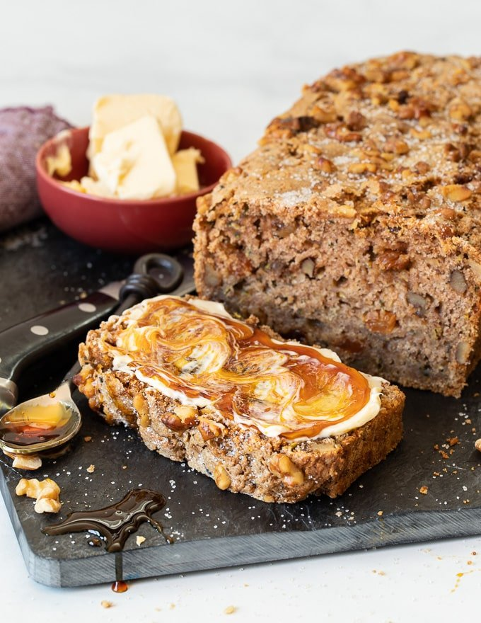 a loaf of vegan zucchini bread with one slice cut off the end and spread with vegan butter and vegan honey