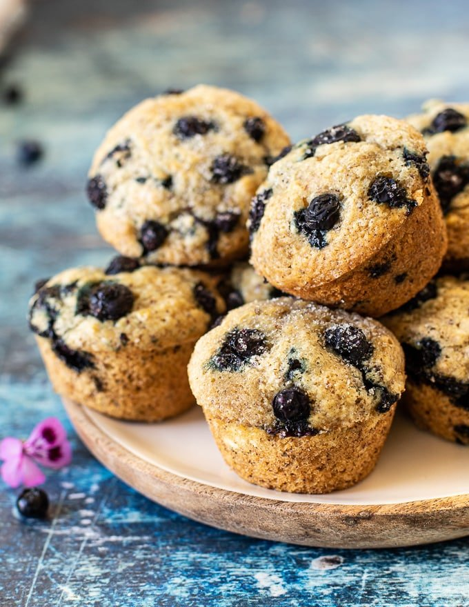 vegan blueberry muffins piled up on a plate