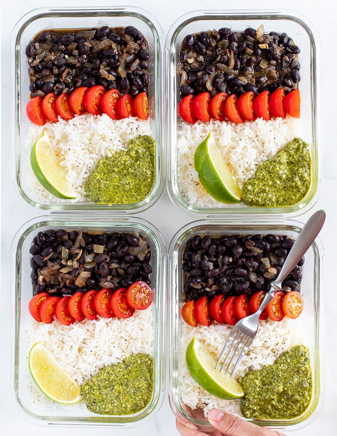 4 glass vegan meal prep containers with rice, black beans, tomatoes and green sauce