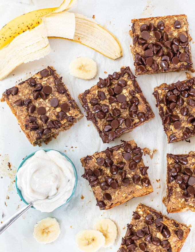 healthy breakfast bars sliced up on a white background with a bowl of yogurt and a banana cut into slices