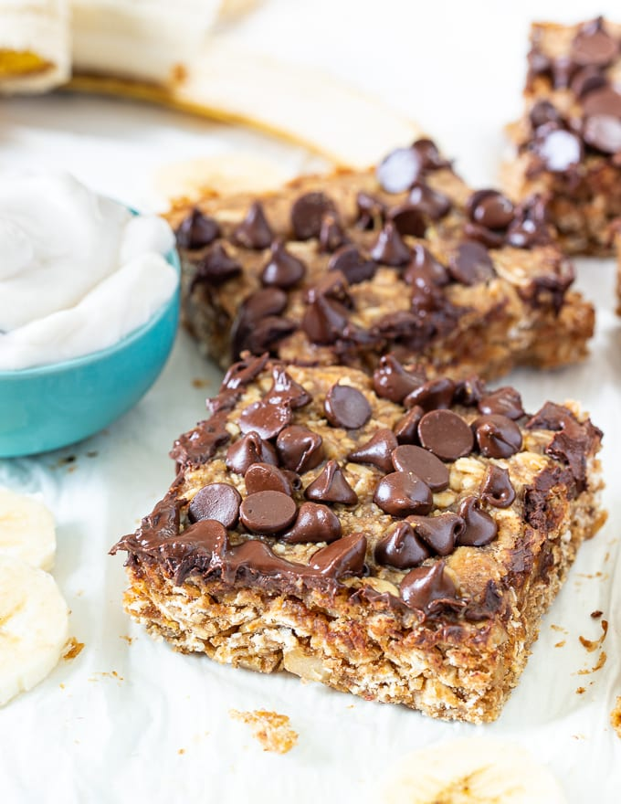 healthy breakfast bars next to a bowl of yogurt
