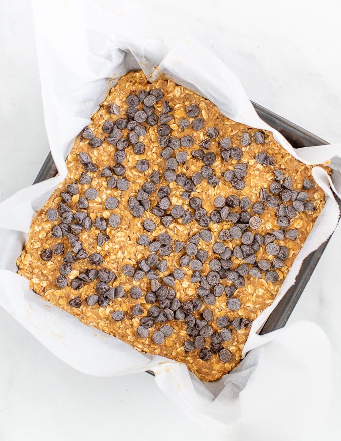 healthy breakfast bar dough in a pan and then topped with chocolate chips