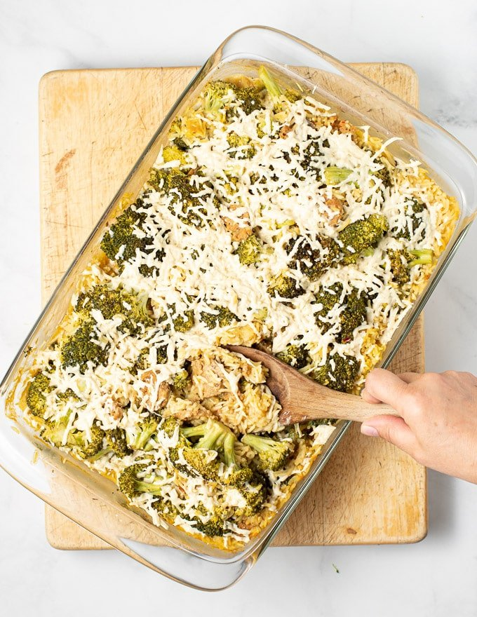 someone spooning out a big helping of vegan broccoli rice casserole