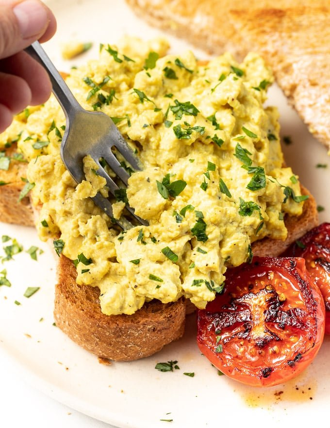 a fork digging into vegan scrambled eggs