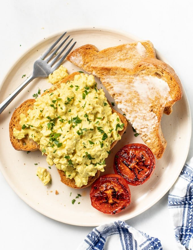 vegan scrambled eggs on toast with grilled tomatoes and a side of buttered toast. Taken form above.
