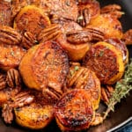 Melting Cinnamon ROasted Sweet Potatoes piled up on a black plate with fresh thyme on the side.
