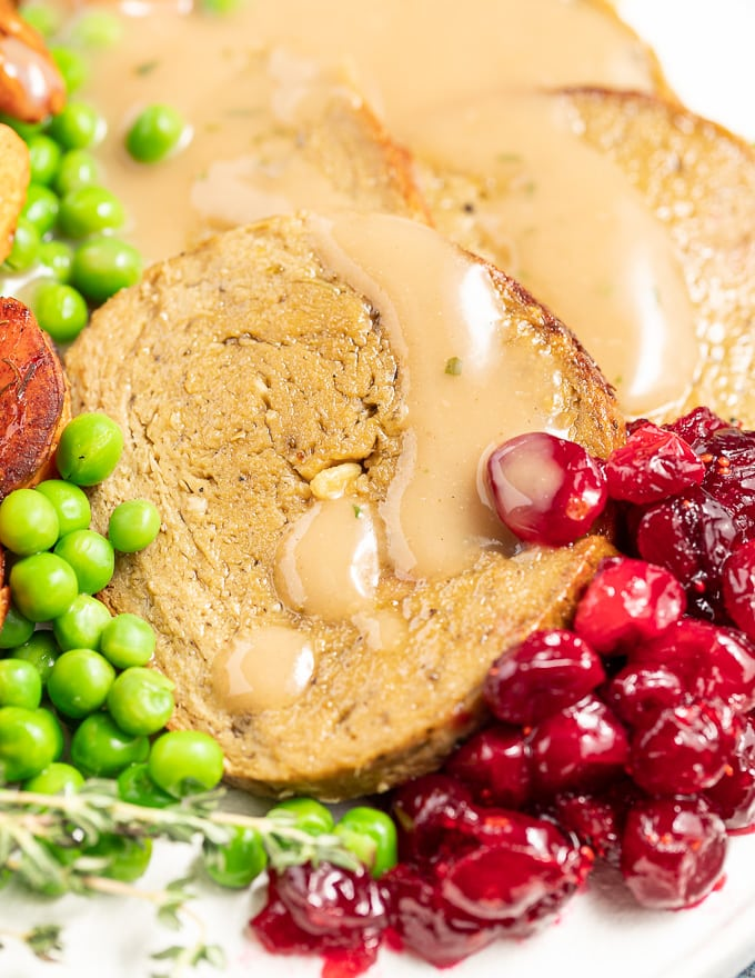 close up of sliced vegan roast, gravy and cranberry sauce