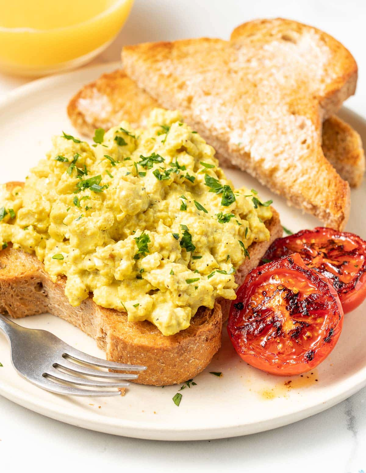 a place of vegan scrambled eggs with tomatoes and a glass of orange juice