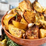 a terracotta colour bowl of roast potatoes with bits of lemon and garlic