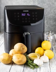 a Cosori air fryer with the ingredients for Lemon Garlic Air Fryer Roasted Potatoes