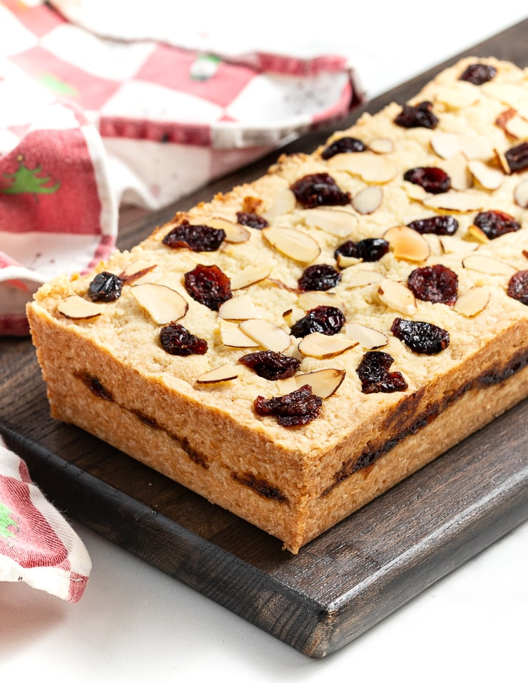 A large bar of Christmas shortbread on a dark brown cutting board