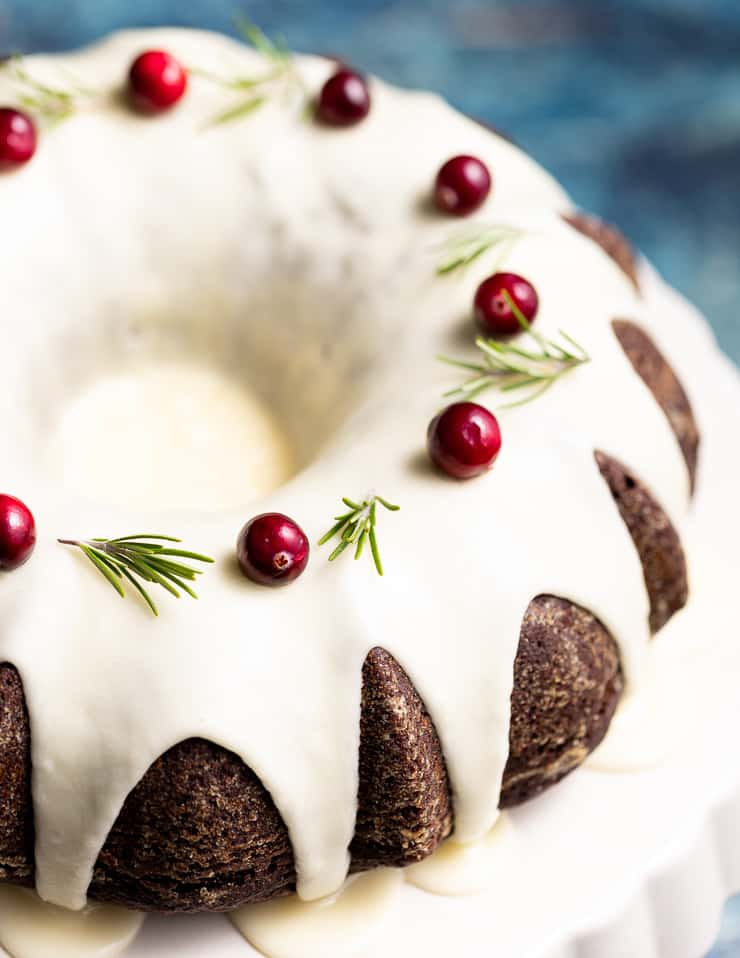 a close up photo of vegan gingerbread cake with orange glaze, cranberries and fresh rosemary