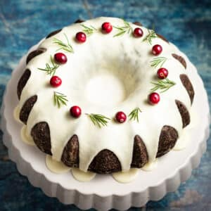 Vegan Gingerbread Cake on a cake stand, topped with glaze, fresh cranberries and rosemary sprigs