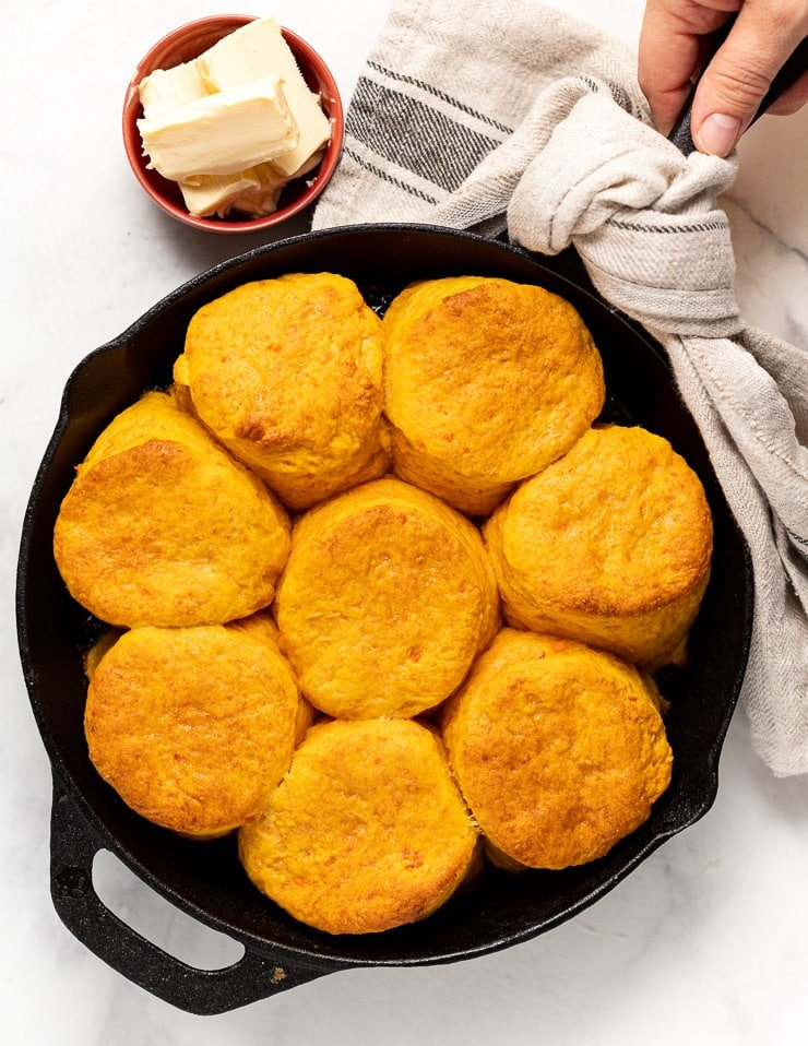 hot cooked vegan sweet potato biscuits in a cast iron skillet next to a bowl