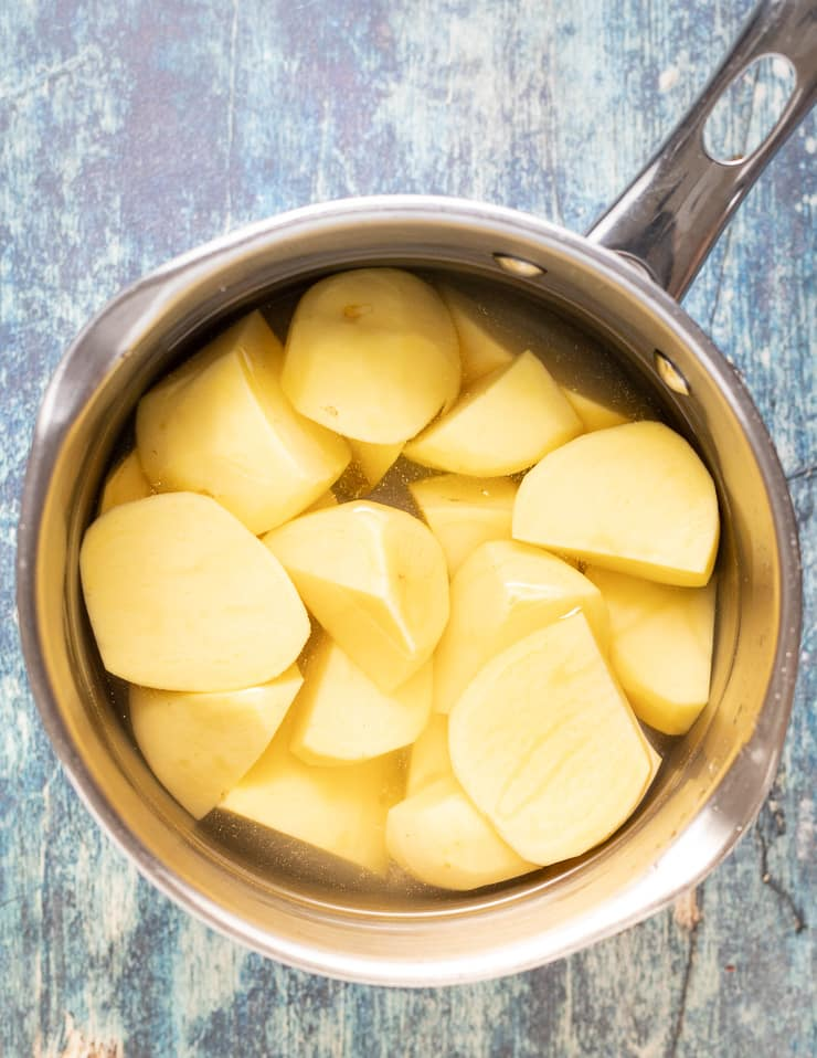 peeled and cut potatoes in a pan of water