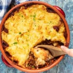 Lentil Shepherd's Pie in a terracotta dish with a wooden spoon digging in