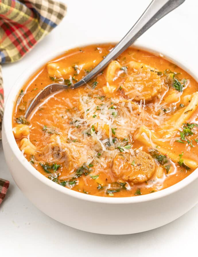 A white bowl full of Vega Italian Sausage Pasta Soup with grated vegan parmesan on top.