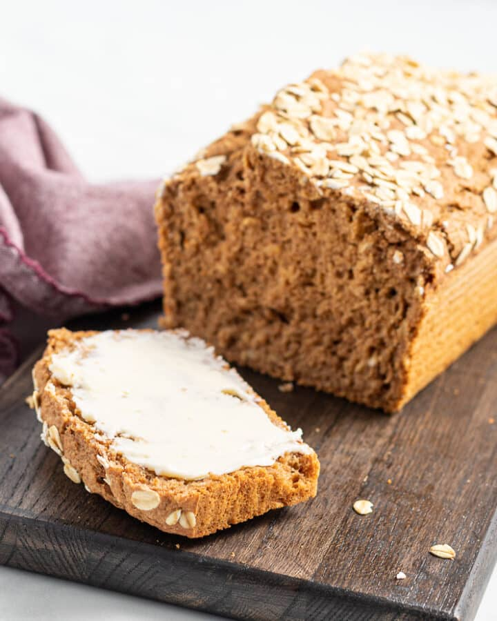a loaf of yeast free spelt bread sliced on a board