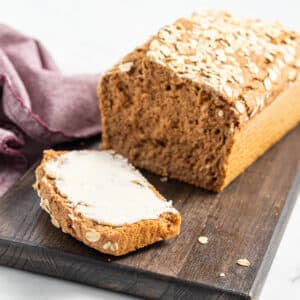 a loaf of yeast-free spelt bread on a board with the end cut off and buttered
