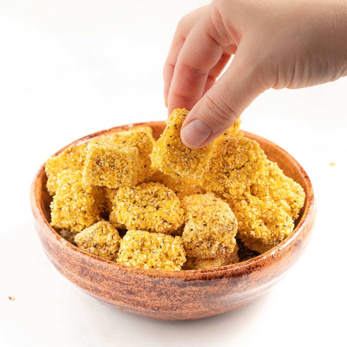 crispy tofu pieces in a brown bowl with a hand taking one