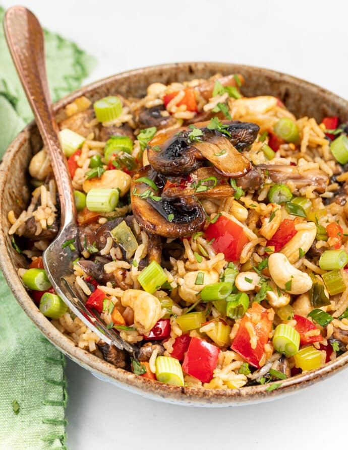 Mushroom Fried Rice in a brown specked bowl with a fork