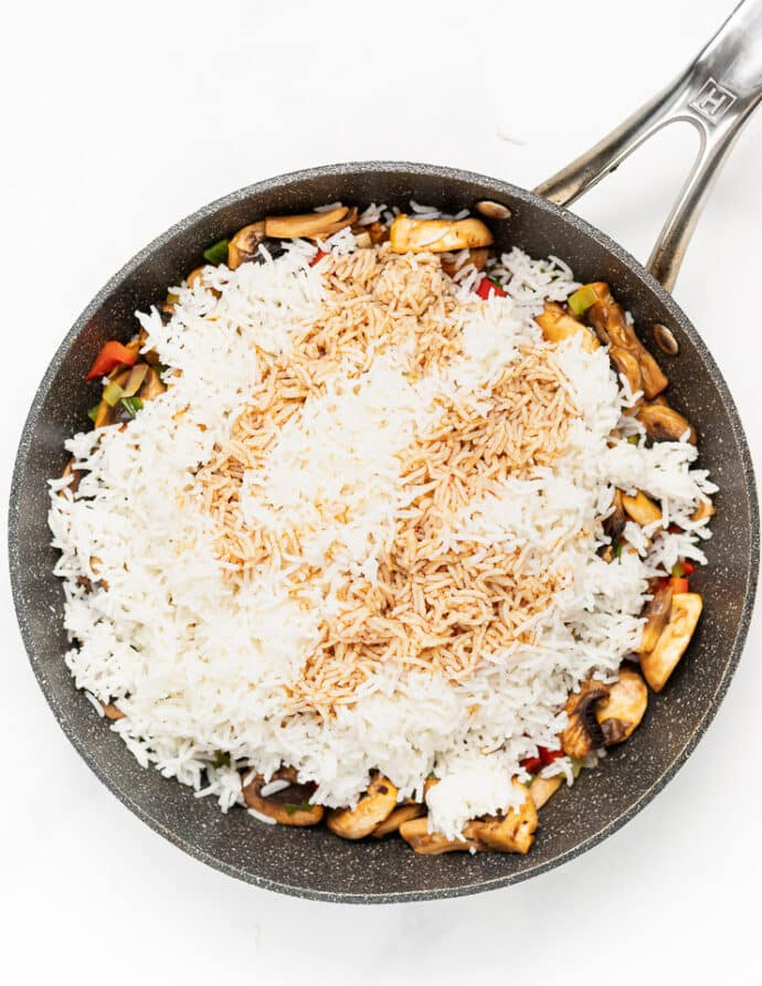 white rice in a pan with vegetables and soy sauce