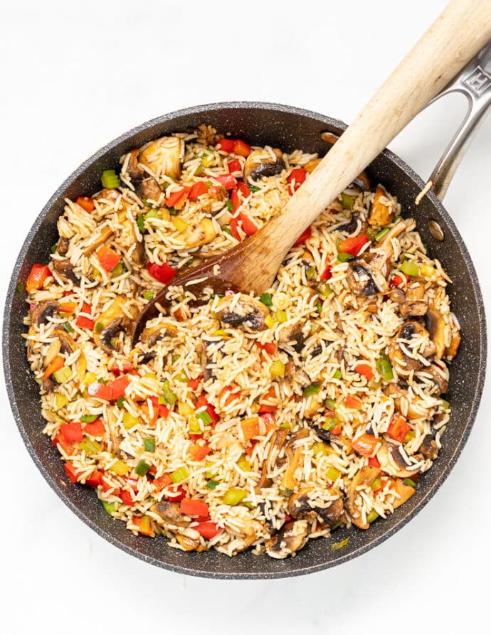 Fried rice in a pan with a wooden spoon