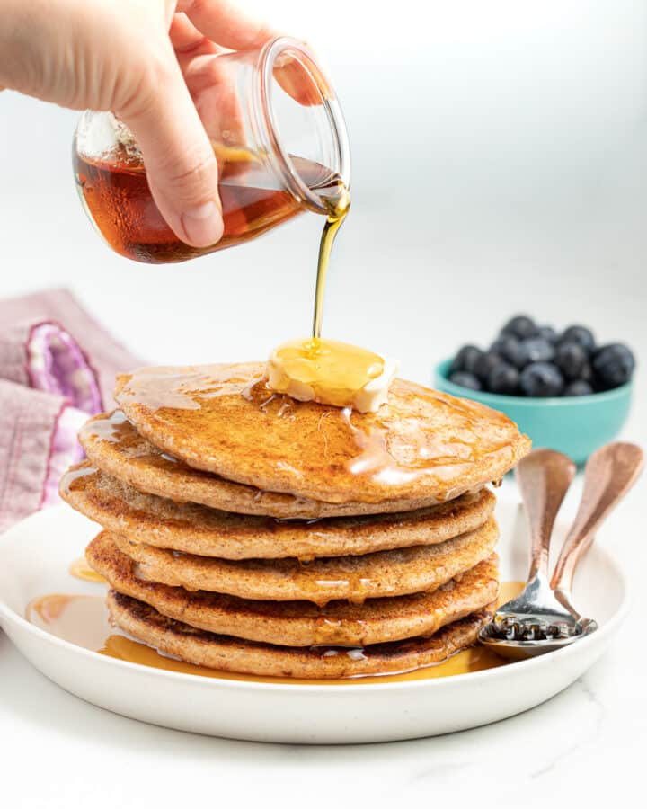 Maple syrup being poured from a small glass jar over a stack of vegan spelt pancakes