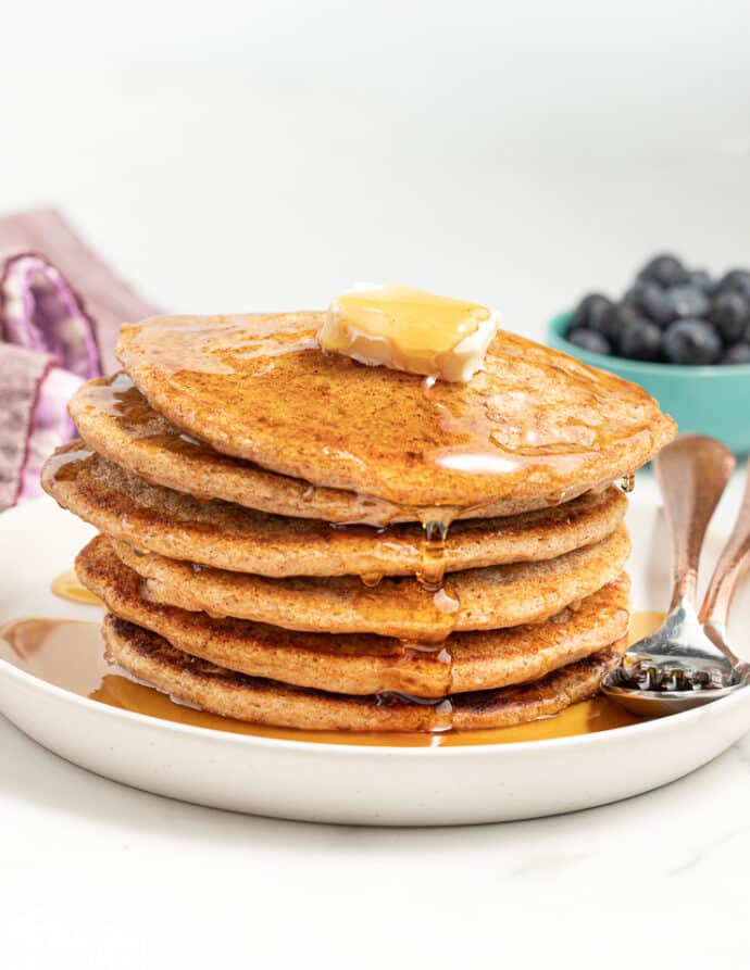 a stack of wholegrain egg-free pancakes with butter and maple syrup