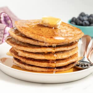 a stack of vegan spelt pancakes with butter and maple syrup