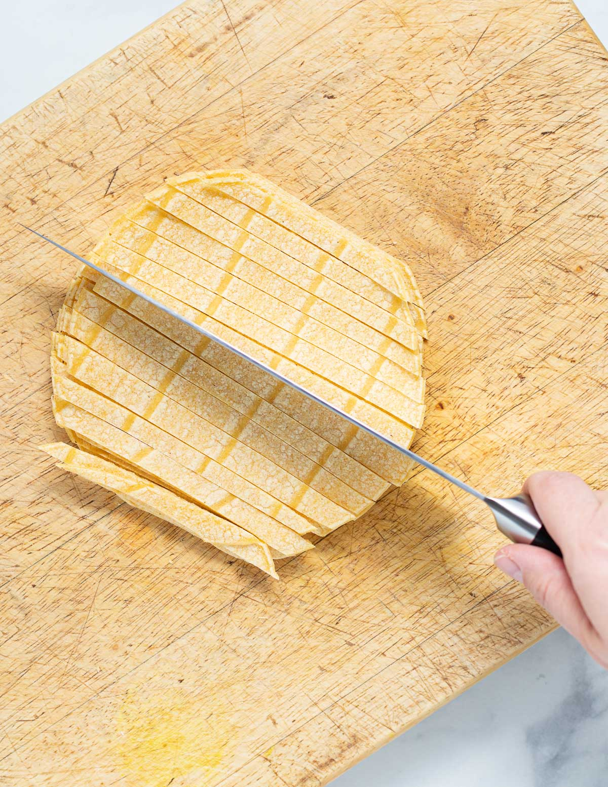 corn tortillas cut into strips on a board