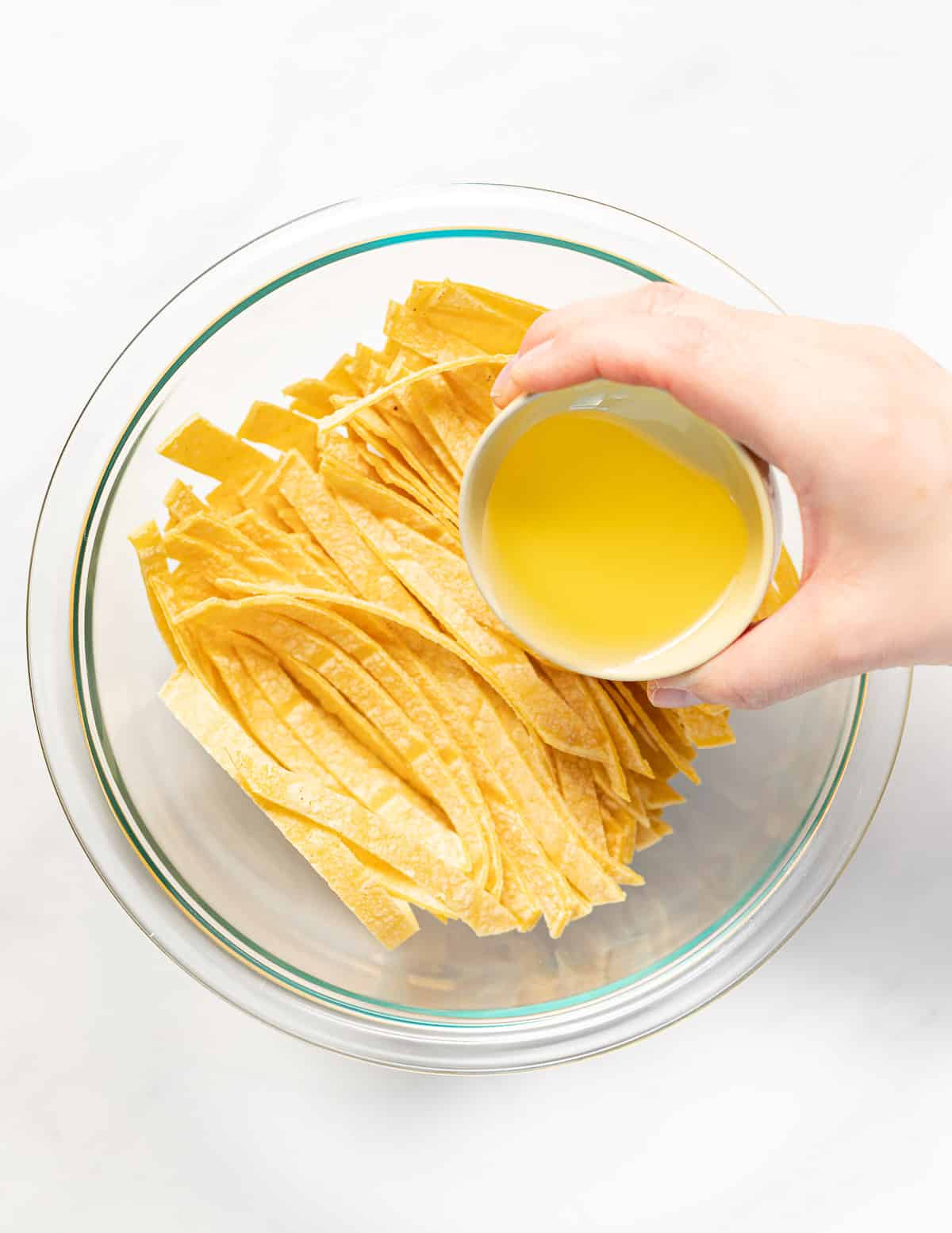 oil being poured over tortilla strips in a bowl
